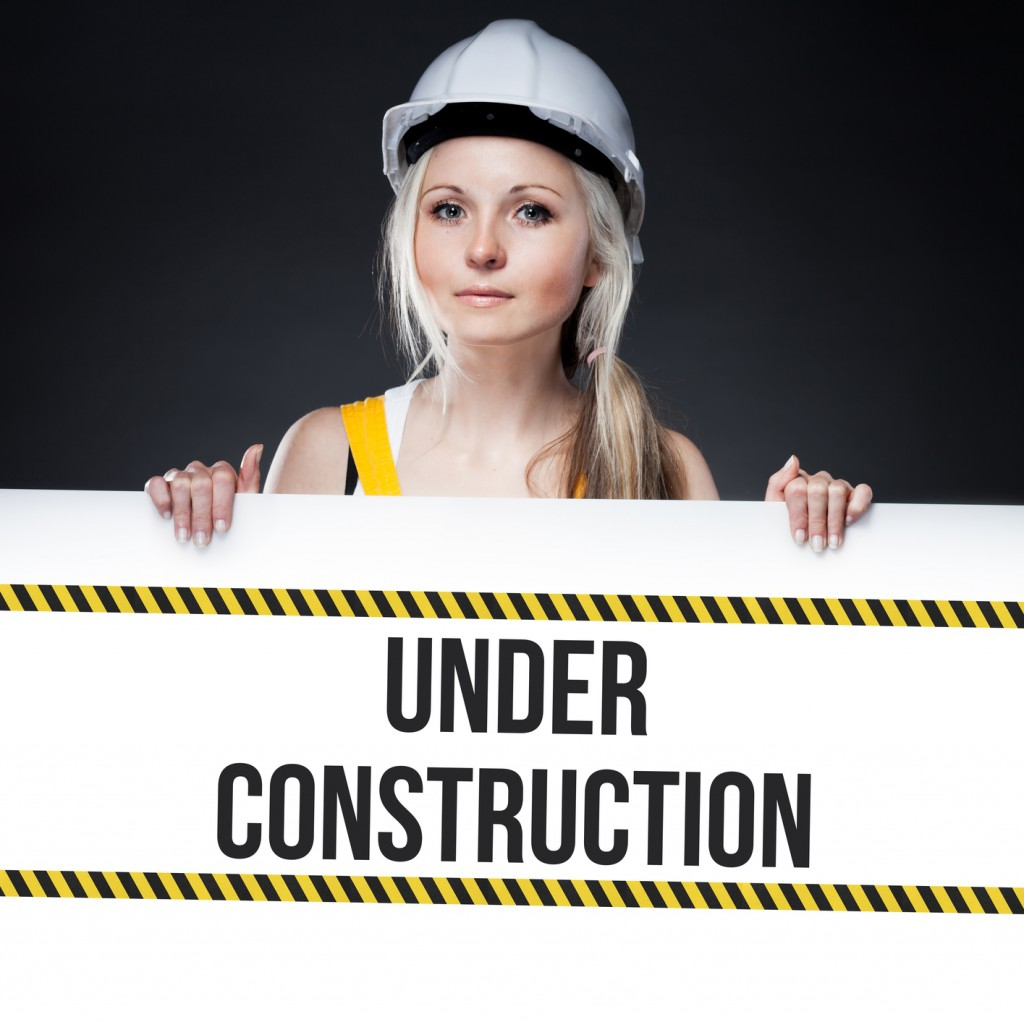 Under construction sign on template board, worker woman