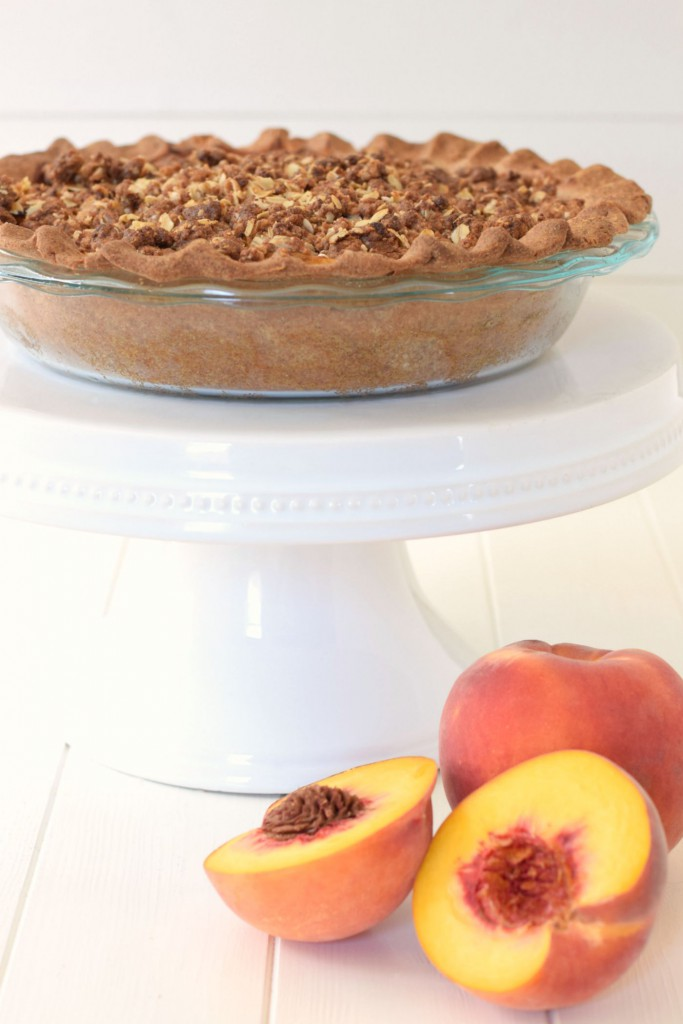 Peach pie and peach cobbler come together in a healthy dessert makeover! This Peach Crumble Pie comes with all the flavor, a flakey crust, and a sweet streusel topping - but with whole grains and no refined sugar!